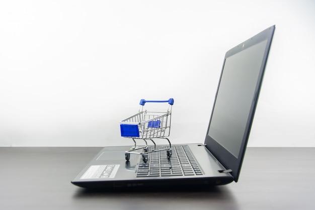 Komputerowy notatnik pusty ekran z wózek na zakupy na drewno stole Premium Zdjęcia