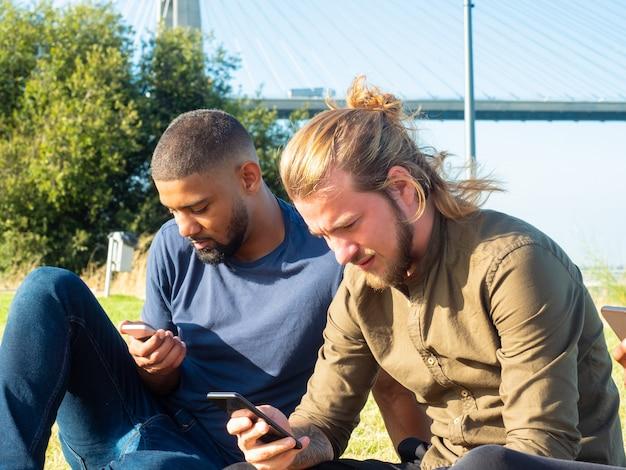 Koncentrujący się mężczyźni używający smartfonów plenerowych Darmowe Zdjęcia