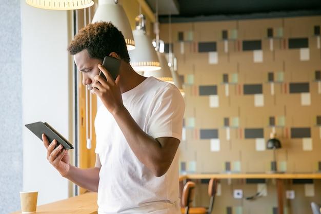 Koncentruje Się African American Facet Rozmawia Na Komórce I Patrząc Na Ekran Tabletu Darmowe Zdjęcia