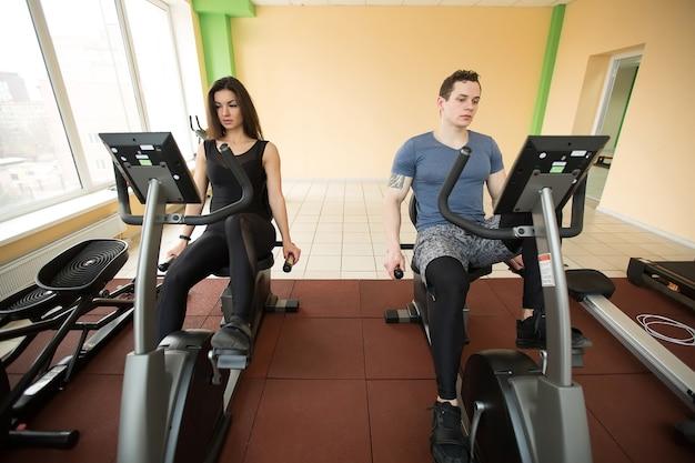 Koncentruje Się Mężczyzna I Kobieta Na Rowerach Stacjonarnych Na Siłowni Premium Zdjęcia