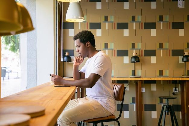 Koncentruje Się Młody African American Człowieka Siedzącego Przy Biurku W Przestrzeni Coworkingowej Lub Kawiarni, Za Pomocą Tabletu Darmowe Zdjęcia