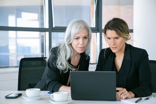 Koncentruje Się Panie Biznesu Patrząc Na Wyświetlacz Laptopa Siedząc Przy Stole Z Filiżankami Kawy W Biurze. Koncepcja Pracy Zespołowej I Komunikacji Darmowe Zdjęcia