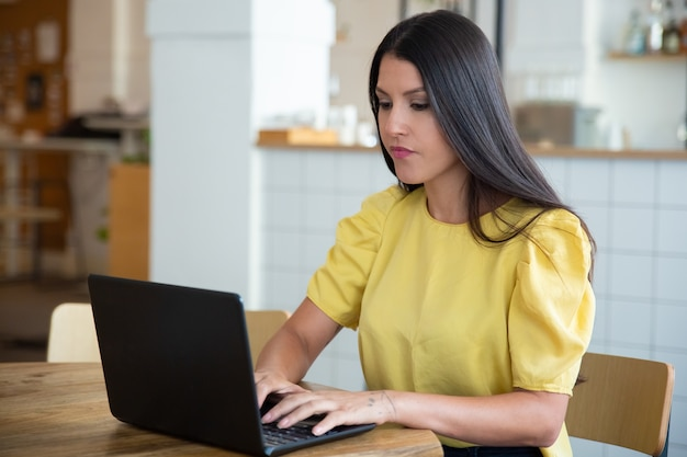Koncentruje Się Piękna Czarnowłosa Kobieta Siedzi Przy Stole W Przestrzeni Coworkingowej, Używając Laptopa, Patrząc Na Wyświetlacz I Wpisując Darmowe Zdjęcia