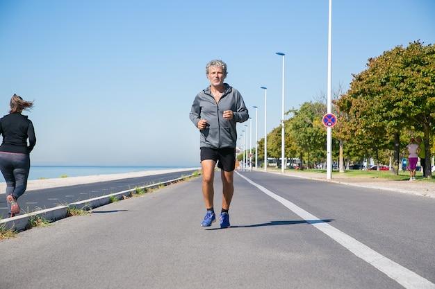 Koncentruje Się Zmęczony Dojrzały Mężczyzna W Strojach Sportowych, Jogging Wzdłuż Brzegu Rzeki Na Zewnątrz. Senior Jogger Trenujący Do Maratonu. Przedni Widok. Koncepcja Aktywności I Wieku Darmowe Zdjęcia
