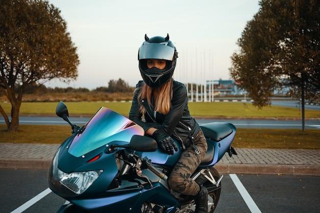 Koncepcja Aktywnego Stylu życia, Ekstremum I Adrenaliny. Zewnątrz Portret Modnej Młodej Blondynki Sobie Dżinsy Khaki, Kask, Czarne Skórzane Rękawiczki I Kurtkę, Pozowanie Na Motocyklu Darmowe Zdjęcia