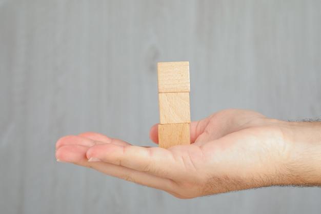 Koncepcja Biznesowa Na Widoku Z Boku Szary Stół. Ręka Trzyma Wieżę Z Drewnianych Kostek. Darmowe Zdjęcia
