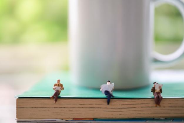 Koncepcja Biznesu, Edukacji, Informacji I Dystansu Społecznego. Trzech Biznesmenów Miniaturowych Ludzi Siedzących I Czytających Książkę I Gazetę Na Stosie Książek Z Kubkiem Gorącej Kawy Z Białym Kubkiem. Premium Zdjęcia