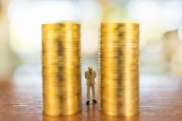 Koncepcja Biznesu, Inwestycji I Planowania. Zakończenie Biznesmen Miniatury Ludzie Oblicza Pozycję Między Stertą Złociste Monety Na Drewnianym Stole Up. Premium Zdjęcia