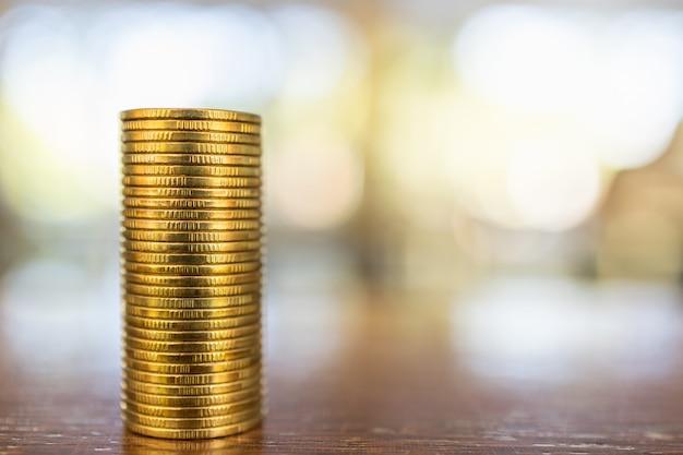 Koncepcja Biznesu, Pieniędzy, Finansów, Bezpieczeństwa I Oszczędności. Zamyka Up Sterta Złociste Monety Na Drewnianym Stole Pod światłem Słonecznym Z Kopii Przestrzenią. Premium Zdjęcia