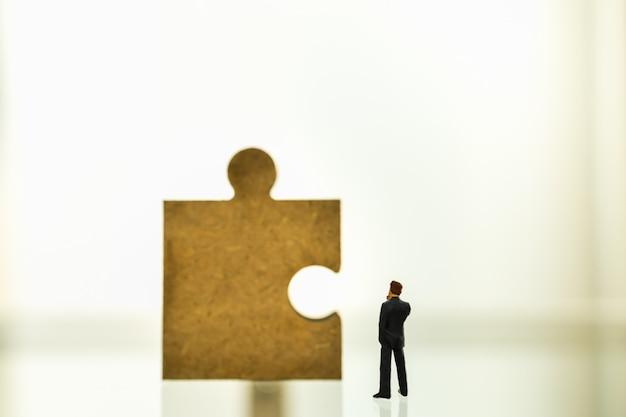 Koncepcja Biznesu, Pracy Zespołowej, Planowania I Pracy. Zakończenie Biznesmen Postaci Miniatury Ludzie Up Stoi I Patrzeje Drewniany Wyrzynarka Kawałek Z Kopii Przestrzenią. Premium Zdjęcia