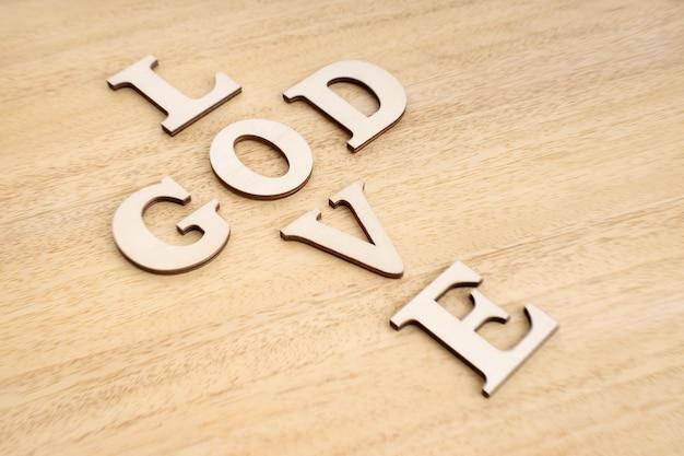 Koncepcja Bóg Jest Miłością. Słowa Tworzące Krzyż Na Drewnianym Stole. Premium Zdjęcia