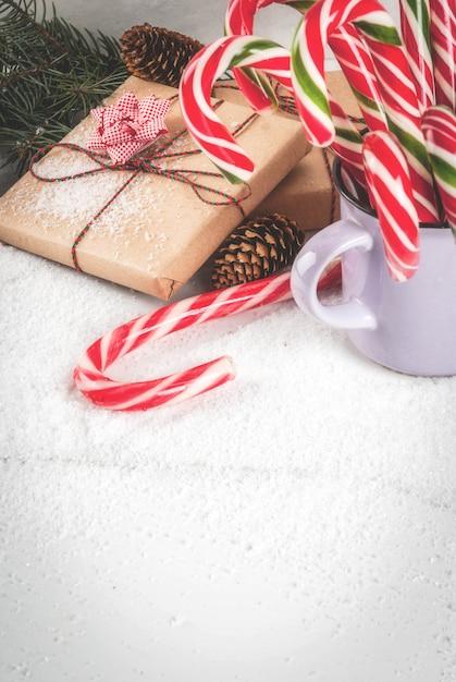 Koncepcja bożego narodzenia, gałęzie choinkowe, szyszki, prezenty i tradycyjne noworoczne słodycze trzciny cukrowej, na białym marmurowym stole ze śniegiem. copyspace Premium Zdjęcia