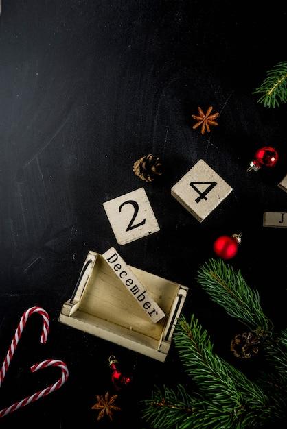 Koncepcja bożego narodzenia z dekoracjami, gałęzie jodły, z kalendarzem 24 grudnia Premium Zdjęcia