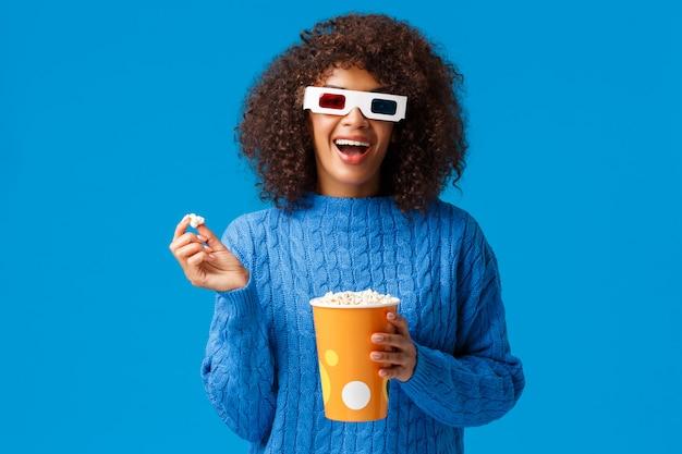 Koncepcja Czasu Wolnego, Stylu życia I Współczesnych Ludzi. Beztroska Zrelaksowana I Radosna, Uśmiechnięta Afroamerykanka Z Fryzurą Afro, Jedząca Popcorn W Kinie, Nosi Okulary 3d I Uśmiecha Się Oglądając Film Premium Zdjęcia