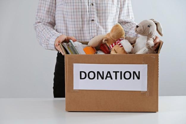 Koncepcja Darowizny. Mężczyzna Trzyma Pudełko Pełne Książek I Zabawek. Podaruj Proszę Dzieciom Premium Zdjęcia