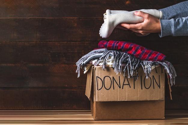 Koncepcja darowizny. pudełko na darowizny z ubraniami do darowizn. dobroczynność. pomaganie biednym i potrzebującym ludziom Premium Zdjęcia