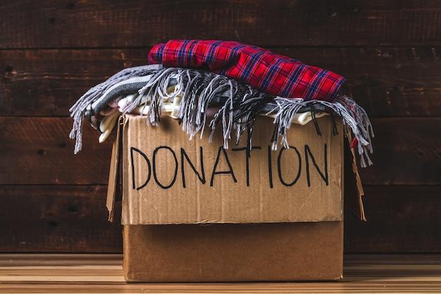 Koncepcja darowizny. pudełko na darowizny z ubraniami do darowizn. dobroczynność. pomoc dla potrzebujących Premium Zdjęcia