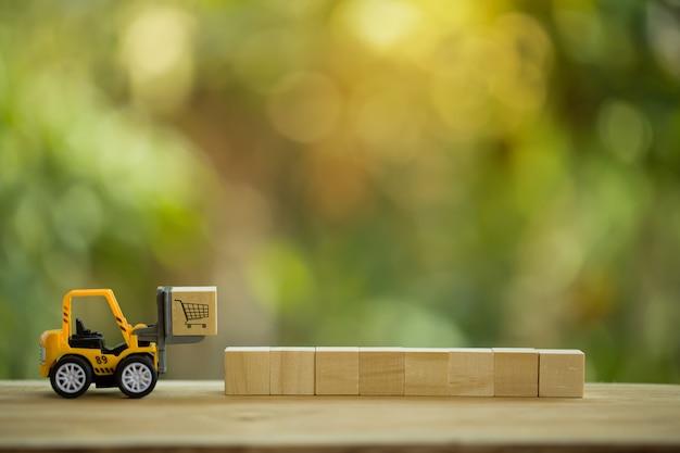 Koncepcja Dystrybucji Sieci Logistycznej I ładunków: Mini Wózek Widłowy Przesuwa Paletę Z Drewnianym Klockiem Z Ikoną. Przedstawia Dostarczanie Towarów Lub Produktów Na Całym świecie W E-handlu. Premium Zdjęcia