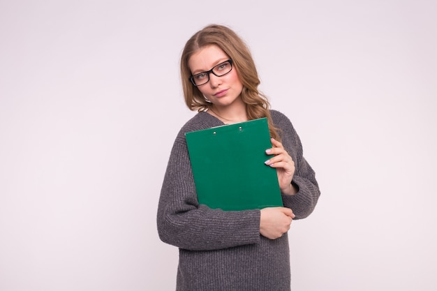 Koncepcja Edukacji, Studentów I Ludzi. Kobieta Na Białym Ubrana W Szary Sweter Trzymać Papierową Teczkę. Premium Zdjęcia