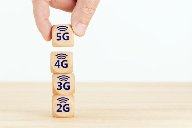 Koncepcja Ewolucji Sieci 5g. Dłoń Trzymająca Drewniany Blok Z Tekstem I Symbolem. Premium Zdjęcia