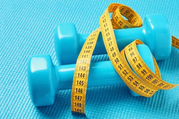 Koncepcja fitness. dumbbells i pomiarowa taśma na błękitnym tle, zamykają up Premium Zdjęcia