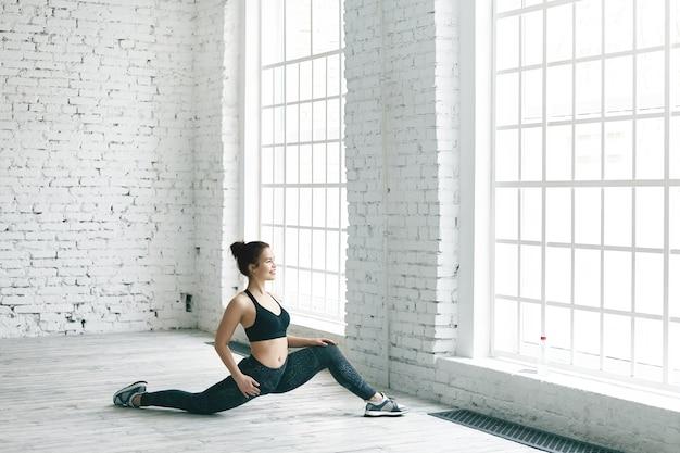 Koncepcja Fitness, Sport, Energia, Zdrowie I Aktywność. Zdjęcie Wesołej Wysportowanej Dziewczyny W Stylowych Trampkach, Bluzie I Legginsach, ćwiczącej W Pomieszczeniu, Rozciągającej Nogi Przed Dużym Oknem Darmowe Zdjęcia