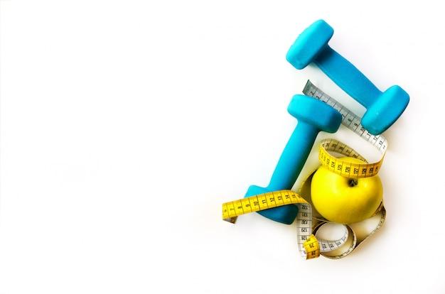 Koncepcja fitness. turkusowi dumbbells, żółta pomiarowa taśma i świeży jabłko. dieta, sport, zdrowy styl życia. wiosenne treningi dla dziewcząt. Premium Zdjęcia