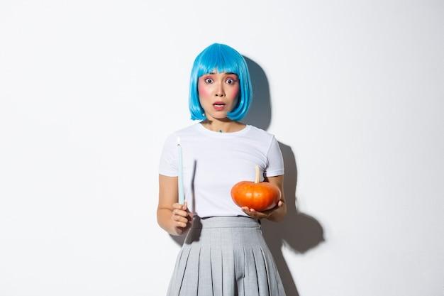 Koncepcja Halloween. Wizerunek Przestraszonej Azjatki W Niebieskiej Peruce Wyglądającej Na Zdenerwowaną I Przestraszoną, Trzymającej świecę I Dyni. Darmowe Zdjęcia
