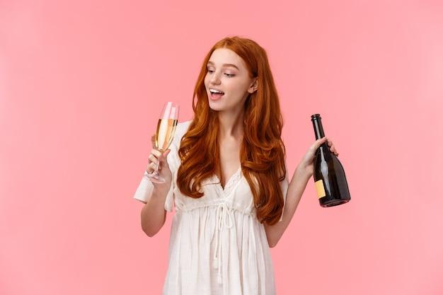 Koncepcja Imprezy, Kaca I Uroczystości. Szczęśliwa I Wesoła, Beztroska, ładna Ruda Kobieta Pije Szampana Ze Szkła, Trzyma Butelkę, Upiła Się, Zmarnowana Stojąc Na Różowo Premium Zdjęcia