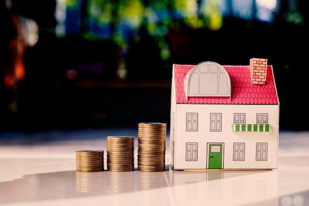 Koncepcja inwestycji w nieruchomości, monety pieniądze rośnie i miniaturowy dom na biurku. Premium Zdjęcia