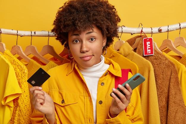 Koncepcja Konsumpcjonizmu, Zakupów I Stylu życia. Nieświadoma Nieświadoma Kobieta Z Kręconymi Włosami Trzyma Kartę Kredytową I Telefon Komórkowy Darmowe Zdjęcia