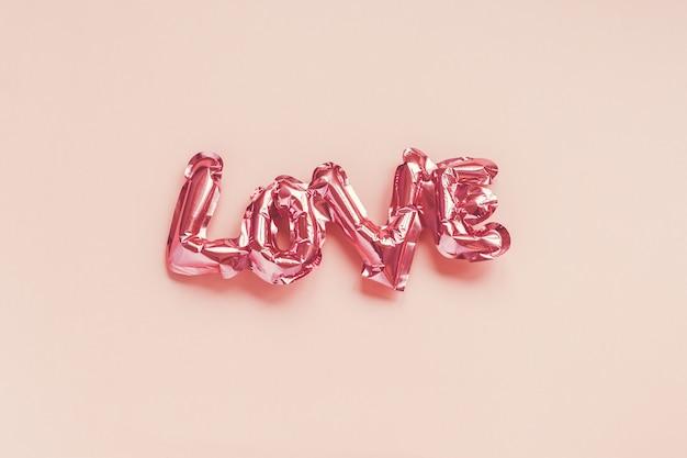 Koncepcja Kreatywna Walentynki. Nadmuchiwany Różowy Błyszczący Balon Foliowy W Kształcie Słowa Miłość Na Różowym Tle. Premium Zdjęcia