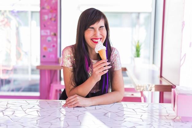 Koncepcja Lata, Młodości I Deseru - Dość śmieszna Dziewczyna Cieszy Się Lody W Kawiarni Premium Zdjęcia