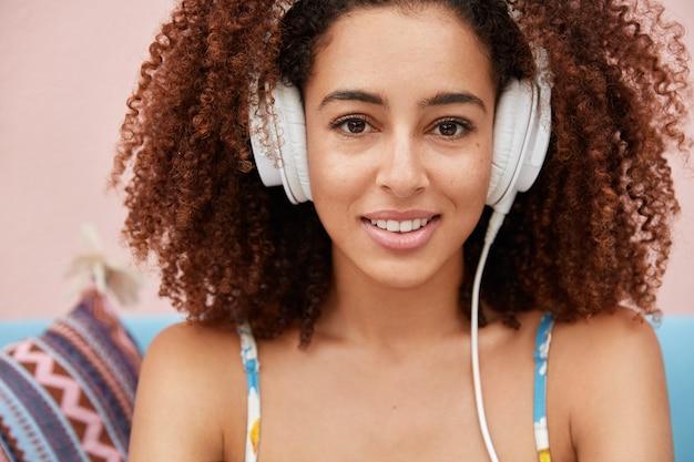 Koncepcja Ludzi, Hobby I Młodzieży. Urocza Młoda Afroamerykanka Z Kręconymi, Krzaczastymi Ciemnymi Włosami, Słucha Ulubionej Muzyki Popularnej W Nowoczesnych Słuchawkach Darmowe Zdjęcia