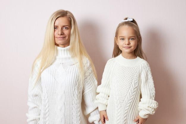 Koncepcja Ludzi I Pokoleń. Pojedyncze Ujęcie Atrakcyjnej Młodej Matki Europejskiej Stwarzających Trzymając Się Za Ręce Z Piękną Córeczką, Oboje Ubrani W Przytulne Ciepłe Swetry Darmowe Zdjęcia