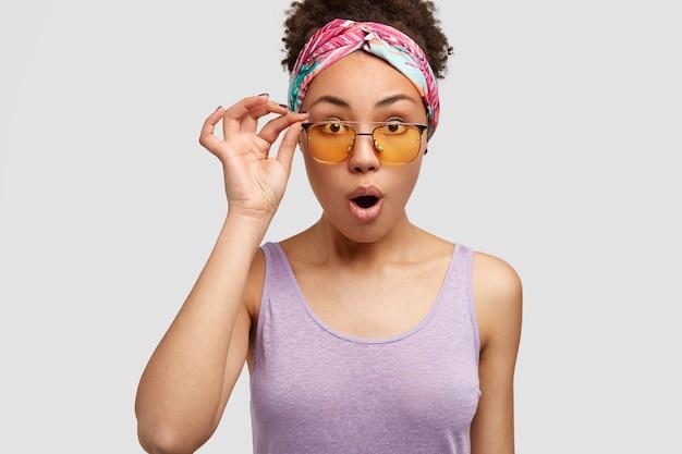 Koncepcja Ludzi, Reakcji I Mimiki. Piękna Przerażona Kobieta O Oszołomionym Wyglądzie, Nosi żółte Odcienie I Fioletową Koszulkę, Patrzy Na Coś Zaskakująco, Pozuje Samotnie Na Białej ścianie Darmowe Zdjęcia