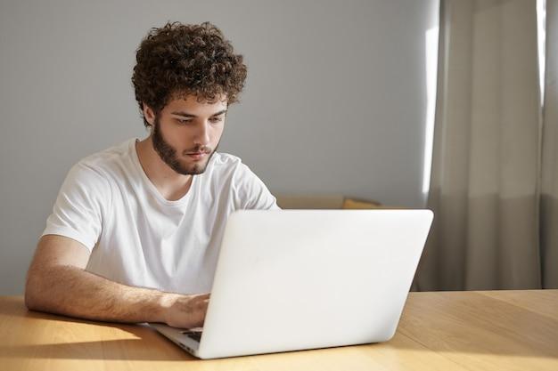 Koncepcja Ludzi, Urządzeń Elektronicznych I Technologii. Szczere Ujęcie Poważnego Przystojnego Młodego Freelancera Korzystającego Z Bezpłatnego Wi-fi Na Laptopie Podczas Pracy Zdalnej Z Domowego Biura, Mając Skoncentrowany Wygląd Darmowe Zdjęcia