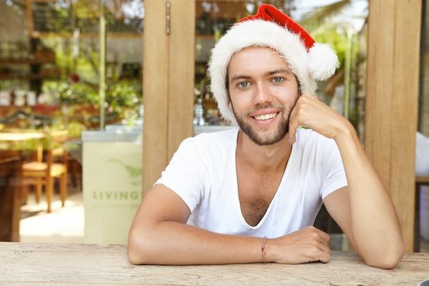 Koncepcja Ludzie, Boże Narodzenie, Nowy Rok I święta. Headshot Atrakcyjny Młody Hipster Ze Stylową Brodą W Czapce świętego Mikołaja, Uśmiechając Się Radośnie Darmowe Zdjęcia