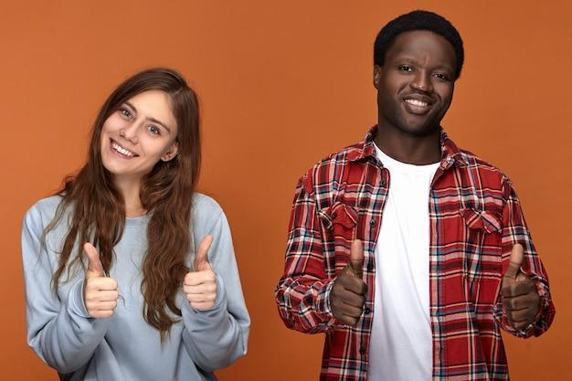 Koncepcja Ludzie, Miłość, Radość, Szczęście I Relacje Międzyrasowe. Dwaj Najlepsi Przyjaciele Z Różnych Grup Etnicznych Robią Kciuki W Górę I Uśmiechają Się, Szczęśliwi Widząc Się Po Długiej Rozłące Darmowe Zdjęcia
