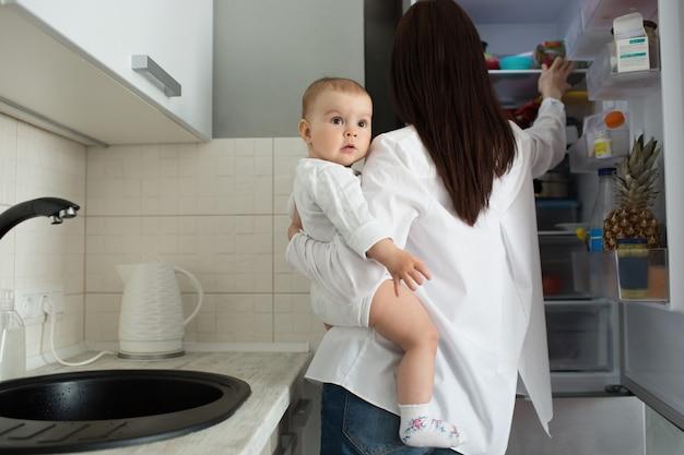 Koncepcja Macierzyństwa I Dzieci. Matka Trzymając Dziecko I Biorąc Jedzenie Z Lodówki Darmowe Zdjęcia