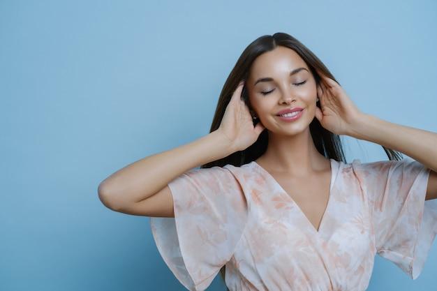 Koncepcja Makijażu, Urody I Mody. Portret Zrelaksowanej Pięknej Kobiety Trzyma Włosy, Stoi Z Zamkniętymi Oczami, Przypomina Coś Przyjemnego, Nosi Modną Sukienkę. Premium Zdjęcia