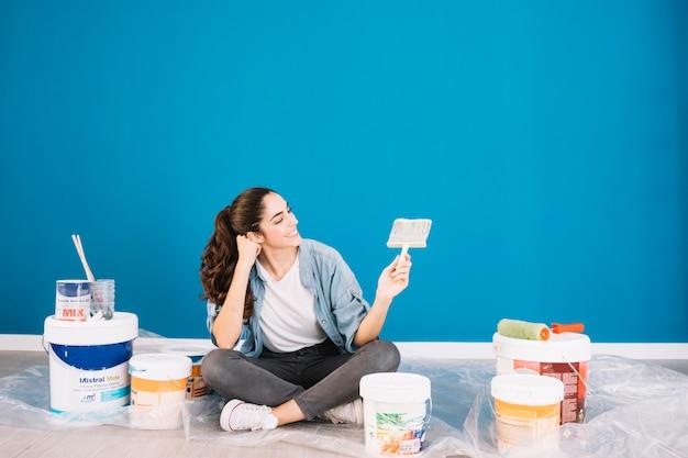 Koncepcja malowania z kobietą patrząc na pędzel Darmowe Zdjęcia
