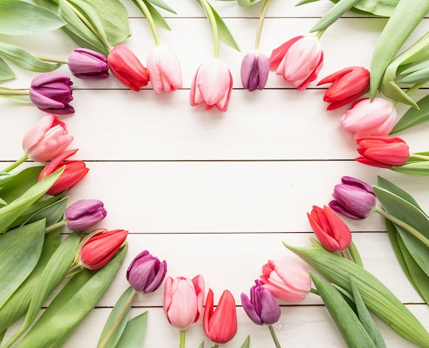 Koncepcja Miłości. Kształt Serca Wykonany Z Wiosennych Kwiatów Tulipanów, Wewnątrz Miejsca Kopiowania. Widok Z Góry Na Płasko Premium Zdjęcia