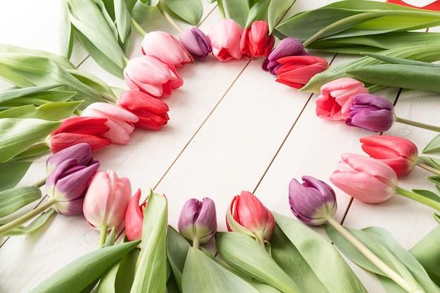 Koncepcja Miłości. Kształt Serca Wykonany Z Wiosennych Kwiatów Tulipanów, Wewnątrz Miejsca Kopiowania. Premium Zdjęcia