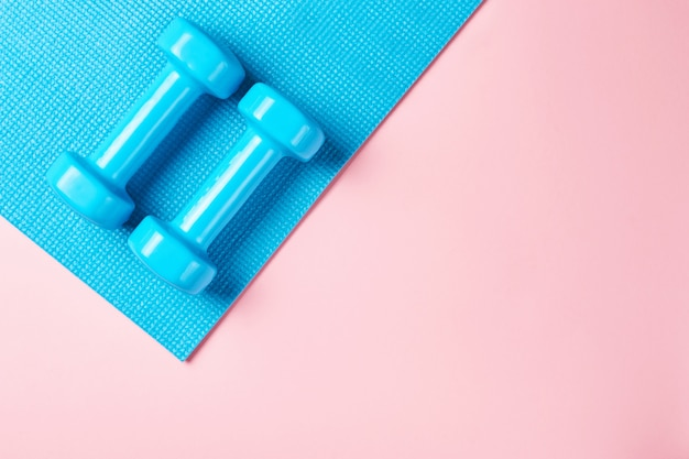 Koncepcja minimalizmu fitnes. dumbbells i sporta stanik na błękitnym i różowym tle Premium Zdjęcia