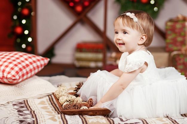 Koncepcja Obchody Nowego Roku I święta Bożego Narodzenia. ładna Mała Dziewczynka W Biel Sukni Bawić Się I Jest Szczęśliwy O Choince I światłach. Ferie. Premium Zdjęcia