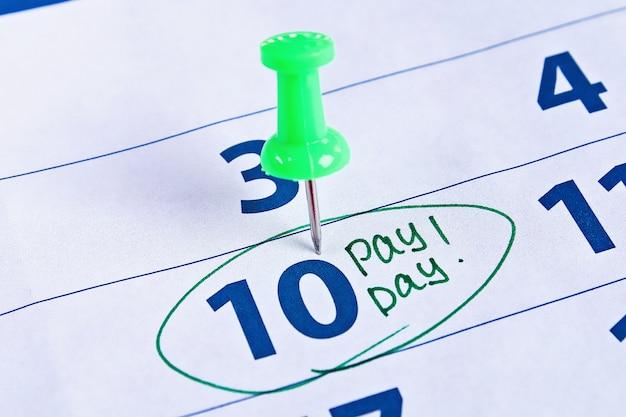 Koncepcja payday. biznes, finanse, oszczędności. kalendarz z kręgu znaczników w słowo wypłaty Premium Zdjęcia