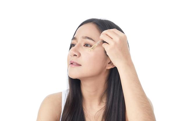 Koncepcja Pielęgnacji Skóry. Piękno Portret Uśmiechnięta Młoda Azjatycka Kobieta Dziewczyna Trzyma Pipetę Z Olejkiem Kosmetycznym Lub Serum W Pobliżu Czystej Twarzy. Kosmetologia I Spa Premium Zdjęcia