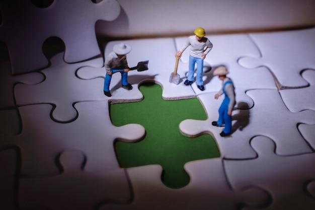 Koncepcja pracy zespołowej i rozwiązywania problemów. miniaturowy pracownik znalazł coś złego Premium Zdjęcia