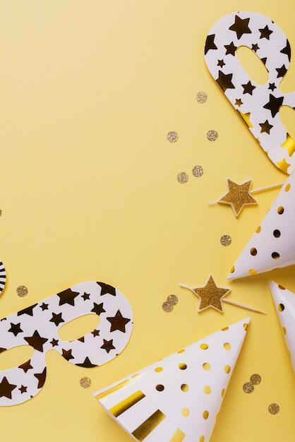 Koncepcja Przyjęcia Urodzinowego Z Czapeczki, Maski I świece Na żółtym Tle. Premium Zdjęcia